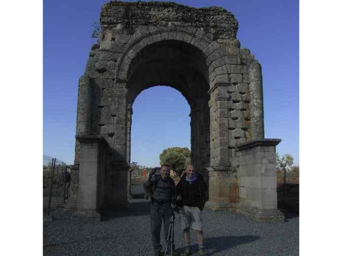 Dos peregrinos bajo el arco de Cáparra